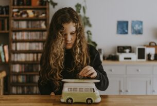 girl wearing black sweatshirt playing toy car